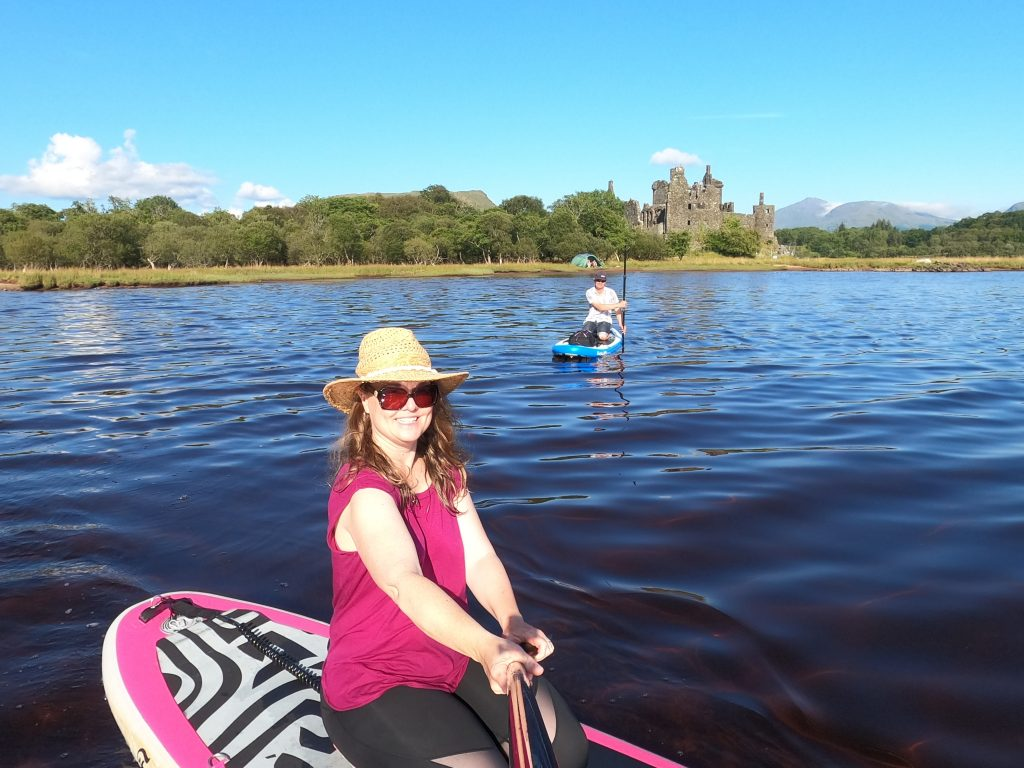 Couple stand up paddleboarding infant of a castle