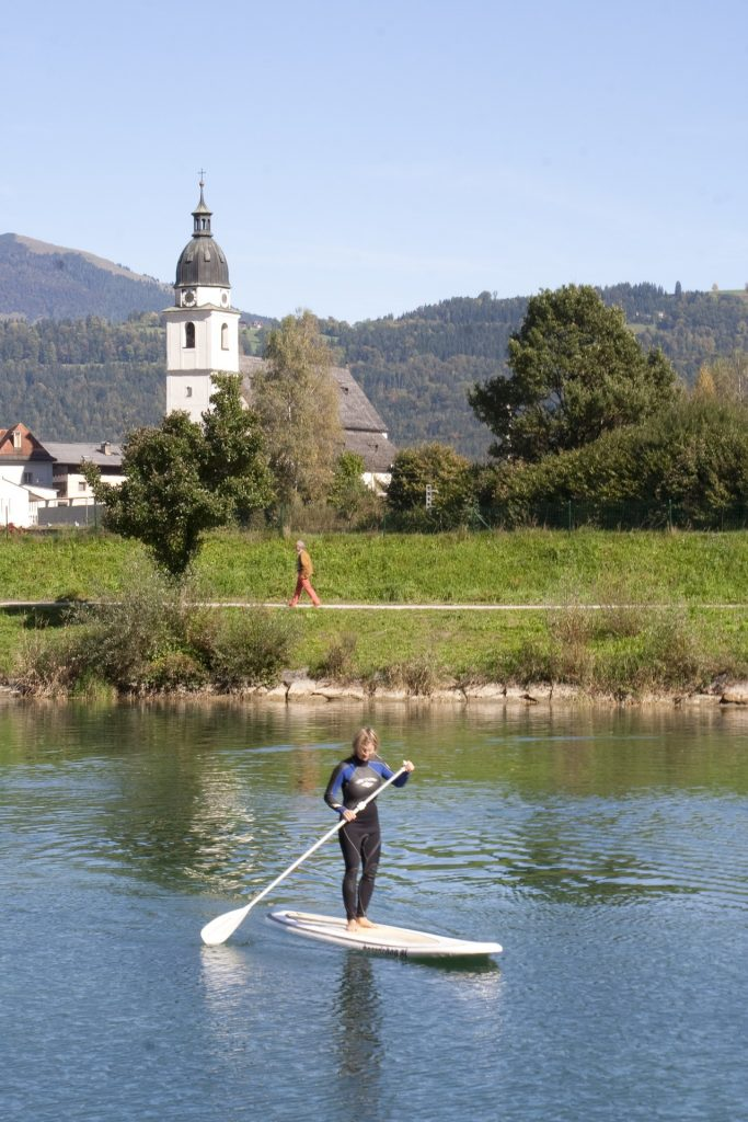 Stand Up Paddleboarder in wetsuit with historic church in background