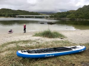 paddleboard on beach with bridge in background