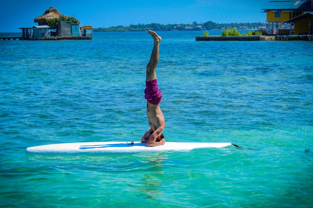 Stand Up Paddleboard headstand for balance and fitness