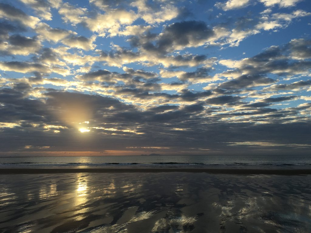 Sun shining through clouds during sunrise at Sarina Beach at low tide