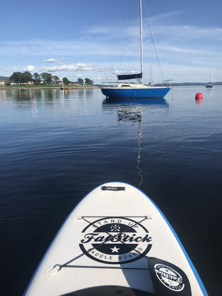 View of sailing boat on Gare Loch from Stand Up Paddleboard