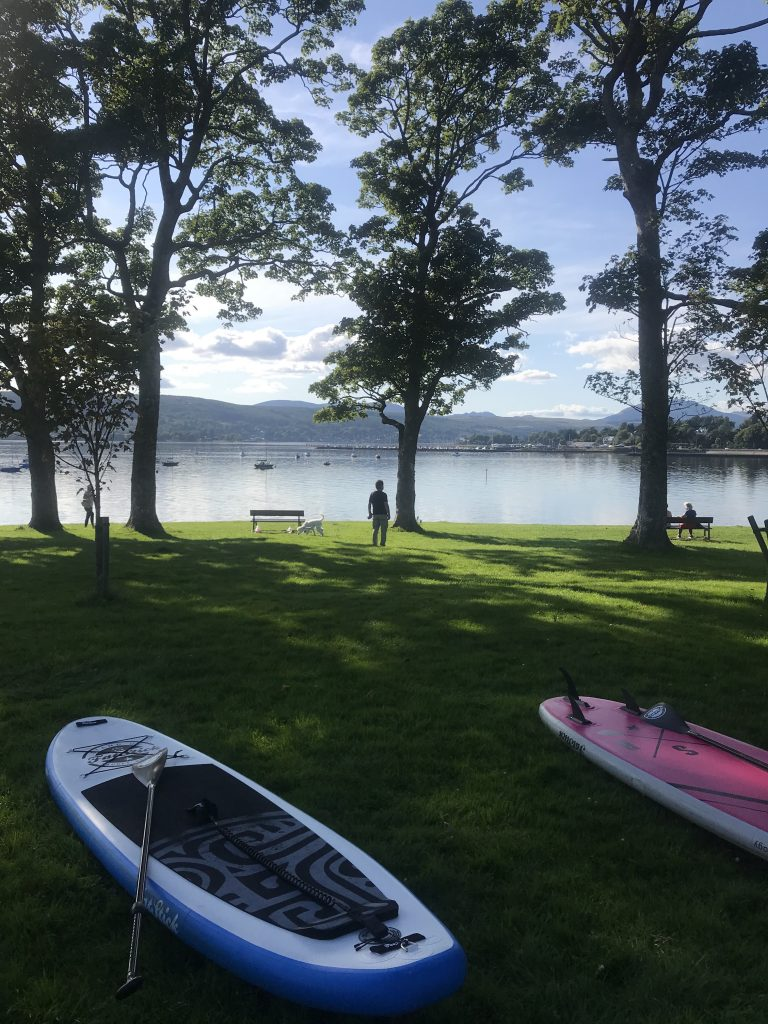 Stand Up Paddleboards in the shade of trees at Kidson Park on Gare Loch