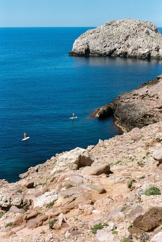 Stand Up Paddleboarding in Majorca with rocky cliff line