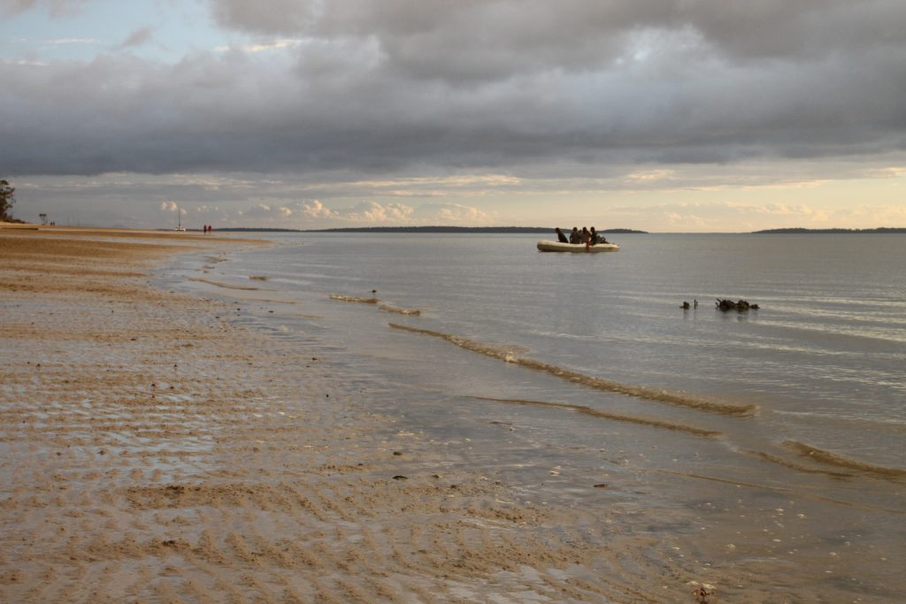 People in a dingy at low tide off the western shore of Fraser Island