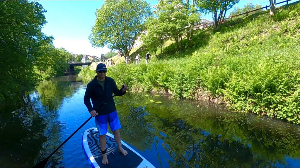 Paddleboarding canal with cyclists in background