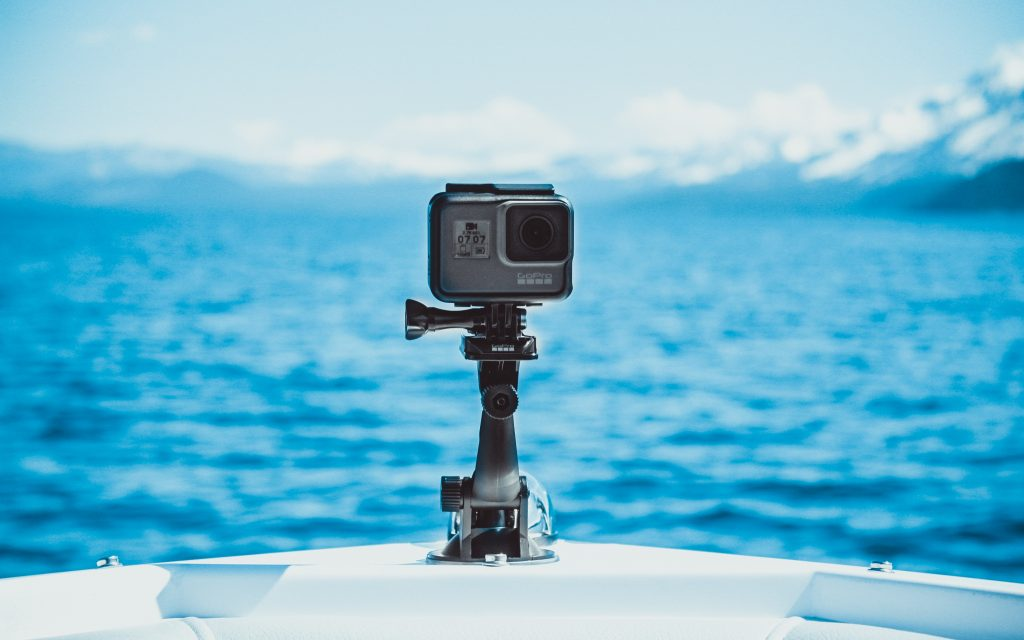 GoPro attached to a boat on a lake surrounded by snowy mountains