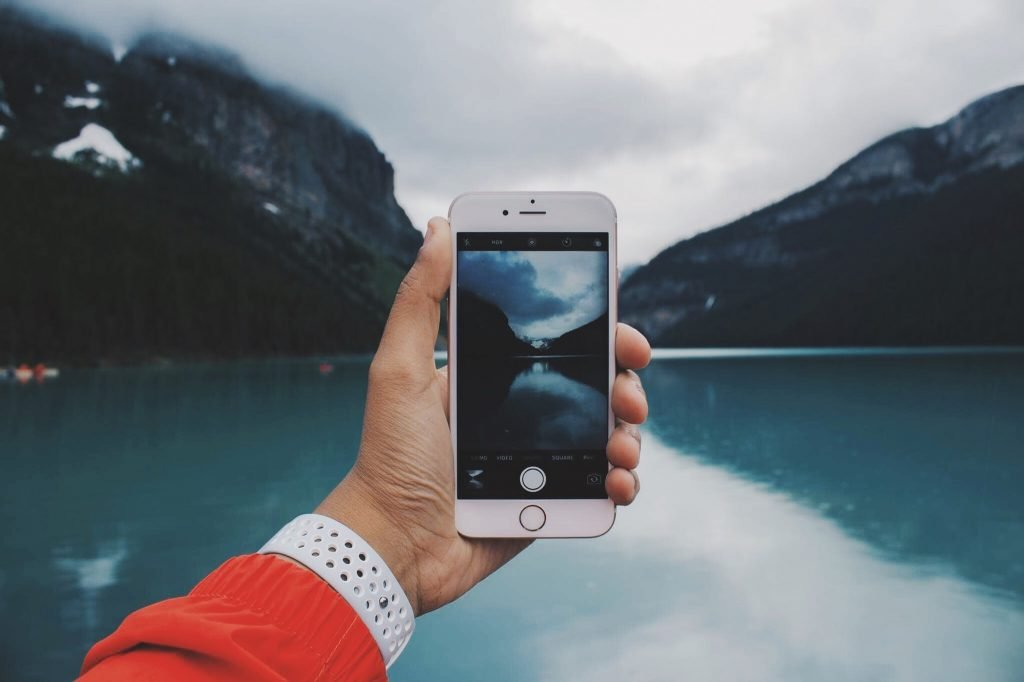 iPhone taking a photo of a lake with mountains