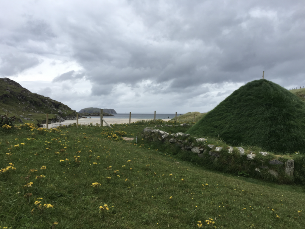 A grass covered Iron Age House with a stone fence overlooking the white sandy Bosta Beach