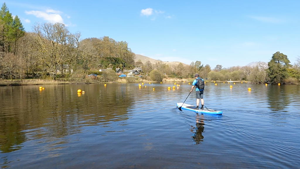 SUP Bloke on paddleboard with buoys and tree lined shore in back ground
