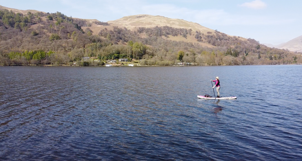 Stand Up Paddleboarding with mountains in back ground on Loch Lomond