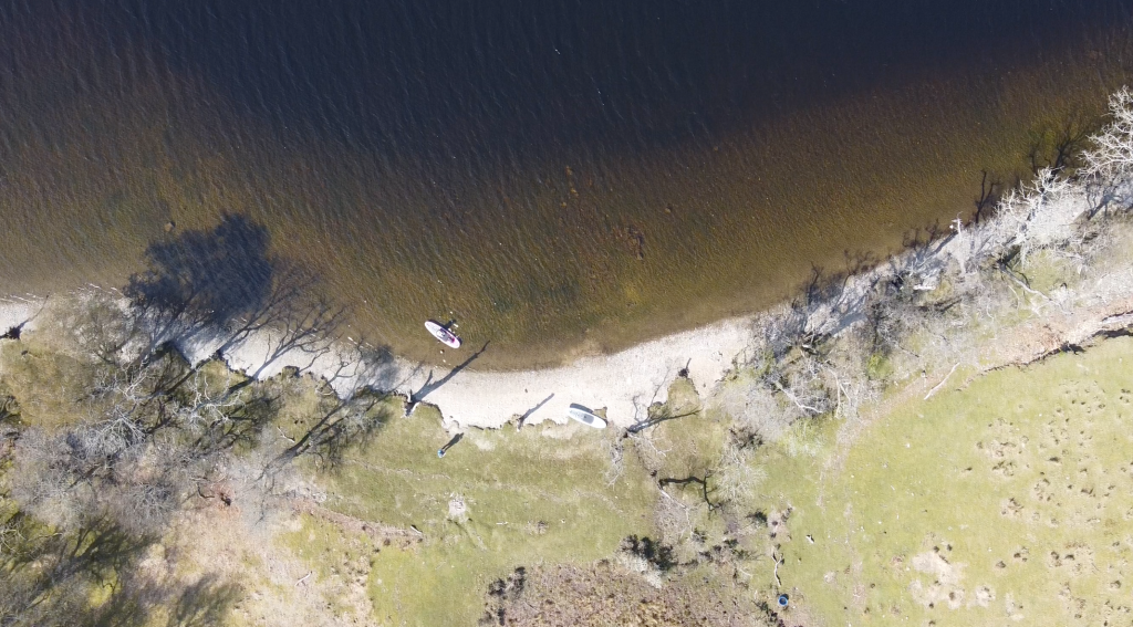 Arial view of paddleboarer on Loch Lomond with shore of island
