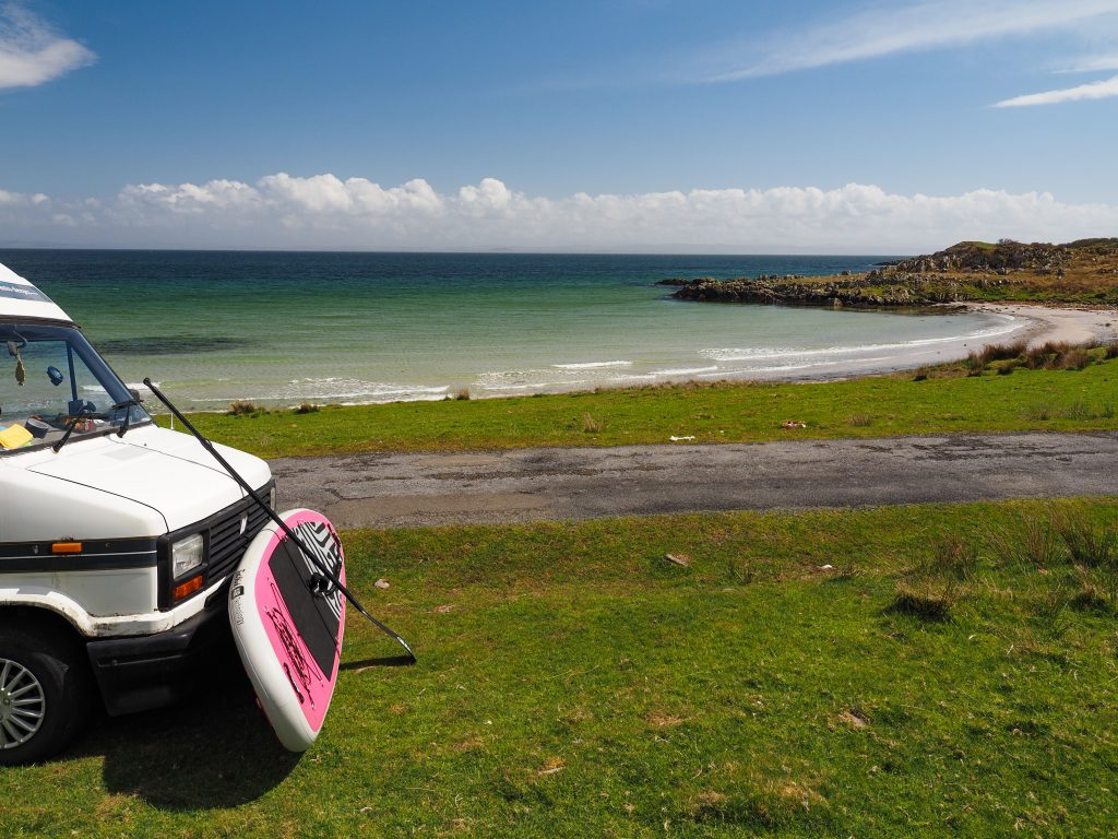 campervan with paddleboard resting on it at sandy bay