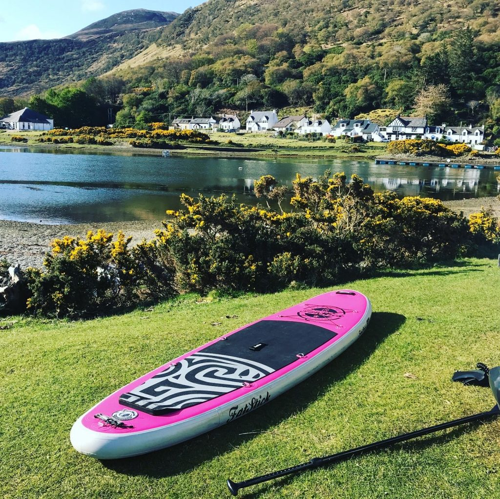 SUP on Isle of Arran with Lochranza harbour and town in back ground