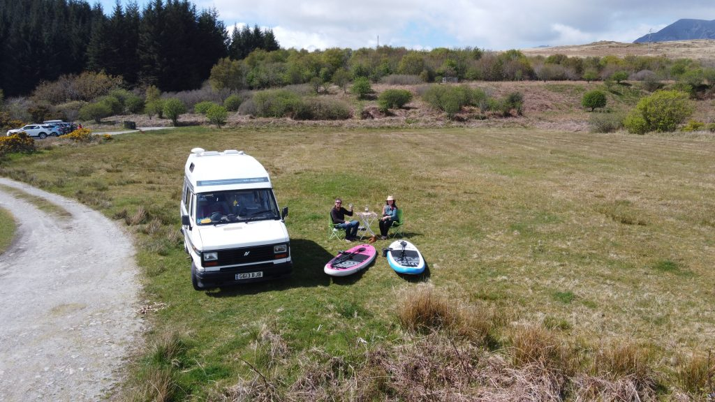 paddle boards camper van and two people having a picnic