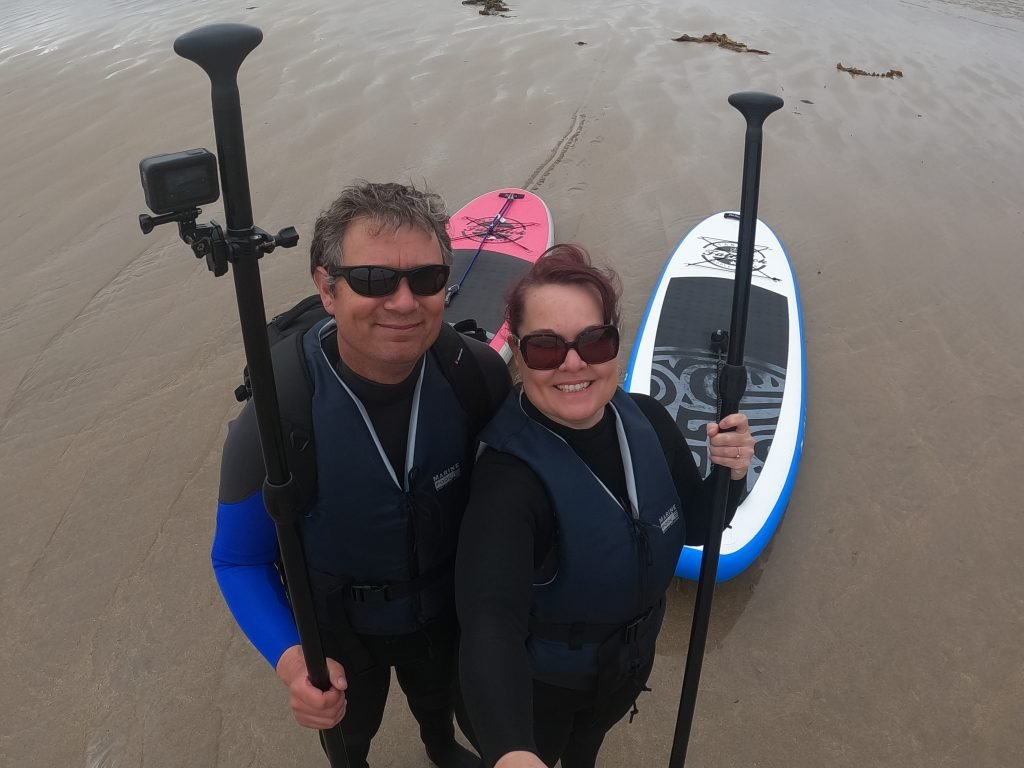 couple with stand up paddle boards on sandy beach