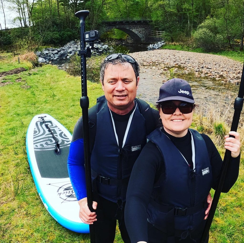 Two paddle boarders with boards, river and ancient stone bridge