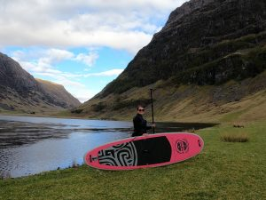 Stand Up Paddle board with paddler and background of Glencoe